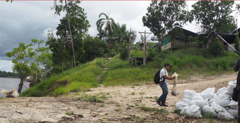 Un miembro de la pastoral de la tierra del Vicariato Apostólico de Yurimaguas (Perú) transporta un saco con vertido de petróleo sacado del río Morona