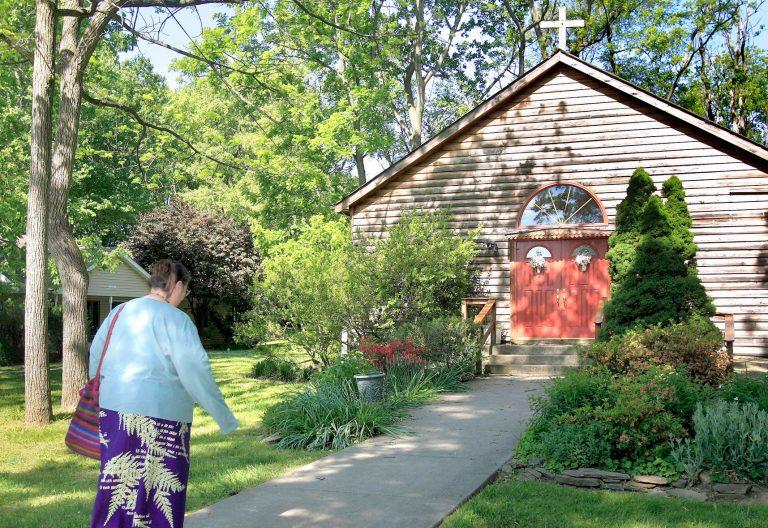 Una mujer se dirige a una capilla en medio del campo para orar
