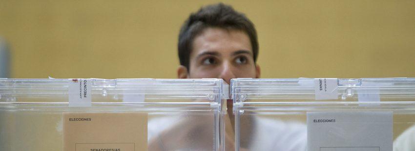 Un joven frente a las urnas en una mesa electoral