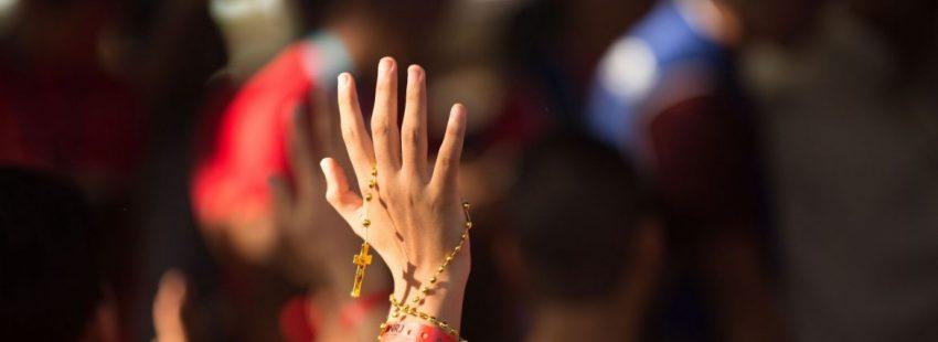 Una joven con un rosario en la mano