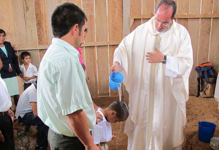 Misionero bautizando a un niño en Perú