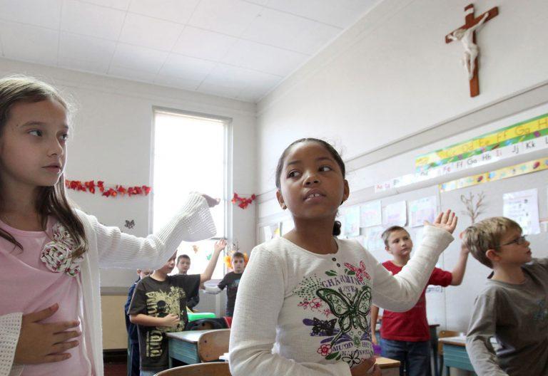 Chicos y chicas bailan en un aula con un crucifijo en la pared