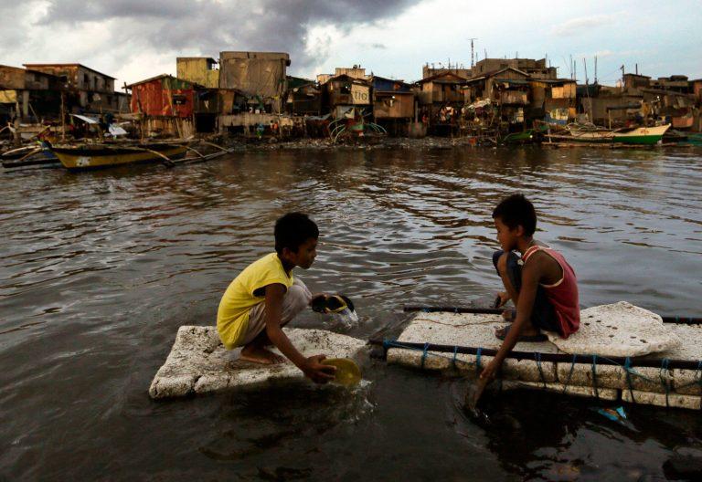 Dos niños flotan sobre aguas contaminadas en los suburbios de Filipinas