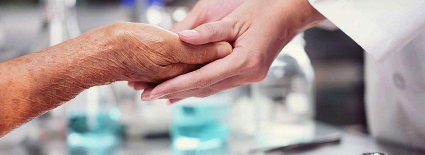 La mano de una enfermera toma la de un enfermo de Cuidados paliativos