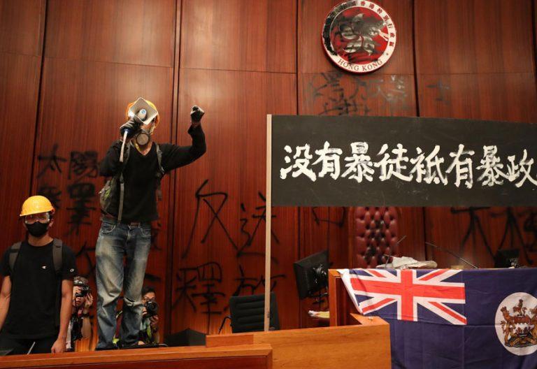 RIT01. HONG KONG (CHINA), 01/07/2019.- Un protestante ofrece un discurso a través de un megáfono tras la irrupción de cientos de manifestantes en el Parlamento de Hong Kong (China), este lunes. Tras pasar más de cuatro horas intentando echar abajo la entrada del edificio con barras de acero, ladrillos o piedras, los manifestantes consiguieron acceder al interior pasadas las 21.00 hora local (13.00 GMT). EFE/ Ritchie B. Tongo