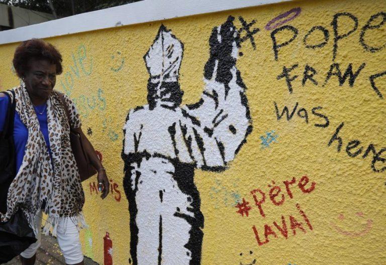 Una mujer, en una calle de Isla Mauricio, frente a un mural con un dibujo del Papa/EFE