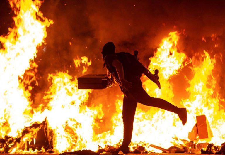 BARCELONA, 15/10/2019.- Un manifestante echa al fuego un cartón junto a la Delegación del Gobierno en Barcelona durante los incidentes producidos al finalizar la movilización convocada por los CDR, hoy martes en la segunda jornada de protestas contra la sentencia condenatoria del Tribunal Supremo a los líderes independentistas del procés. EFE/Enric Fontcuberta
