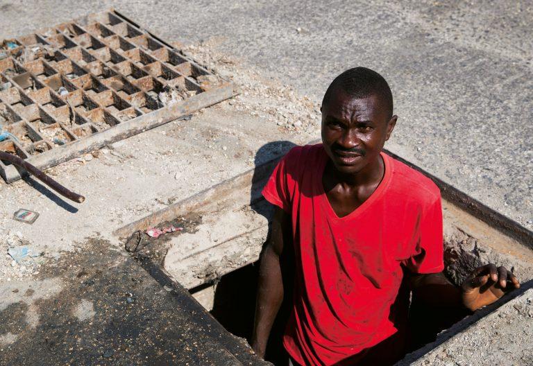 Un hombre limpiando las alcantarillas en las calles de Haití