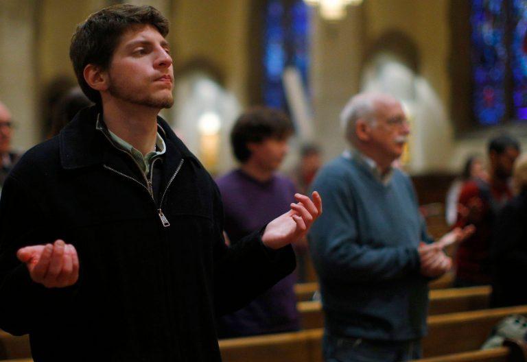 Un joven y varias personas mayores rezan en una iglesia semivacía