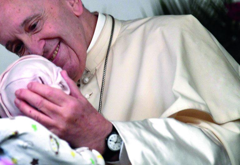 Francisco acaricia el rostros de una bebé