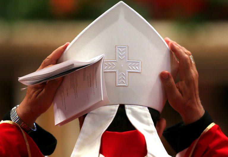 Un obispo de espaldas ajustándose la mitra