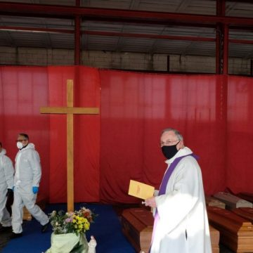 Ponte San Pietro (Italy), 03/04/2020.- A priest wearing a protective face mask blesses the coffins of people who died of coronavirus, before they are taken away to the crematory ovens in other Italian regions with military trucks, in Ponte San Pietro, near Bergamo, northern Italy, 03 April 2020. Italy is under lockdown in an attempt to stop the widespread of the SARS-CoV-2 coronavirus which causes the Covid-19 disease. (Italia) EFE/EPA/FILIPPO VENEZIA