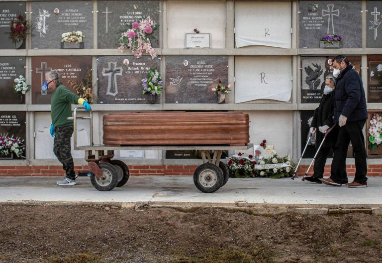 Dos familiares de una víctima del coronavirus acompañan el ataúd en el cementerio