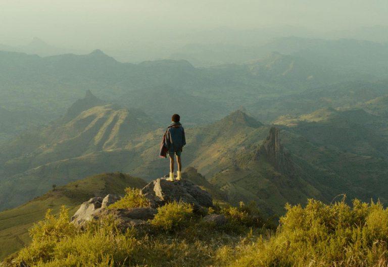 Un niño contempla el horizonte desde la cima de una montaña