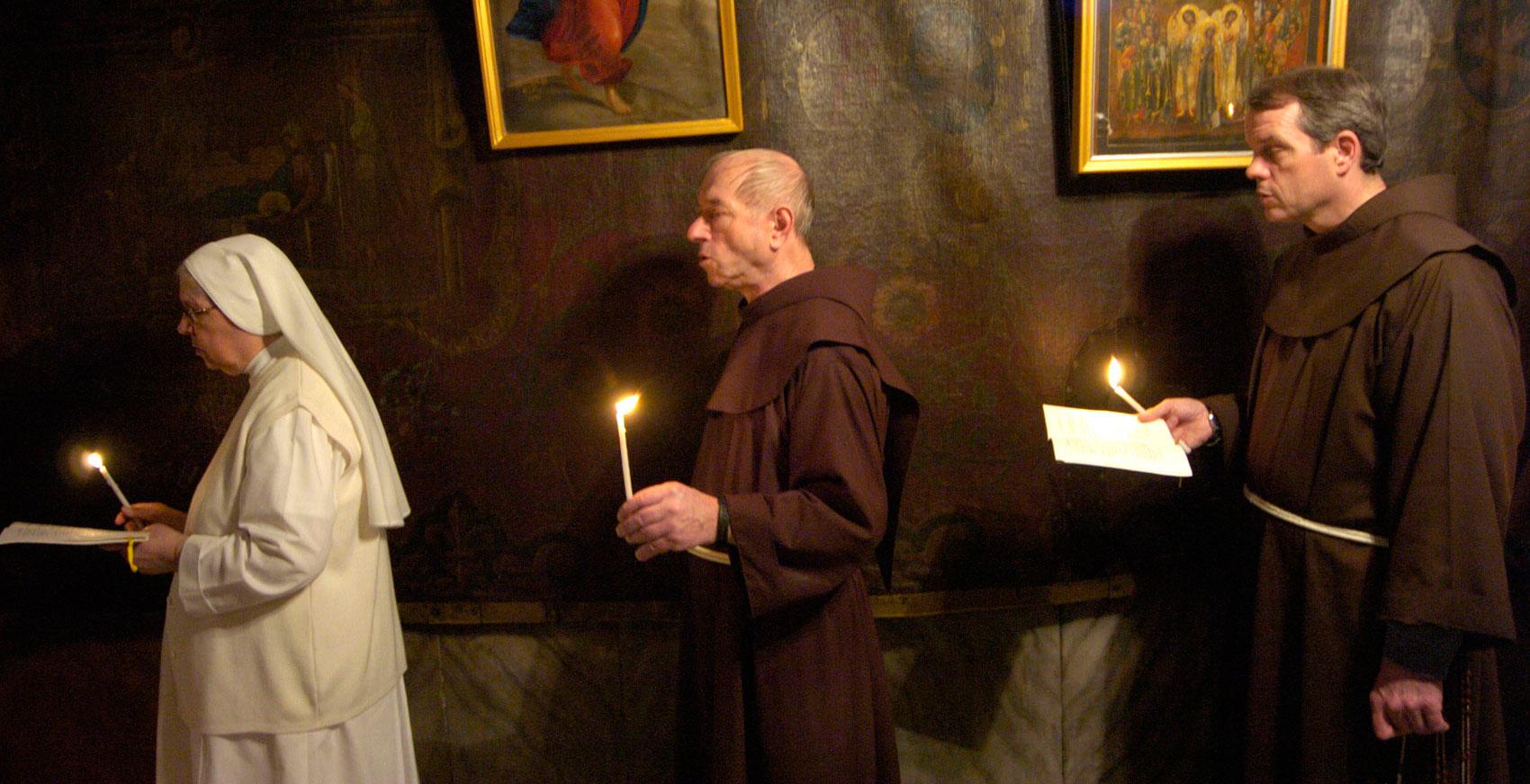 Dos frailes y una monja durante una vigilia en Tierra Santa