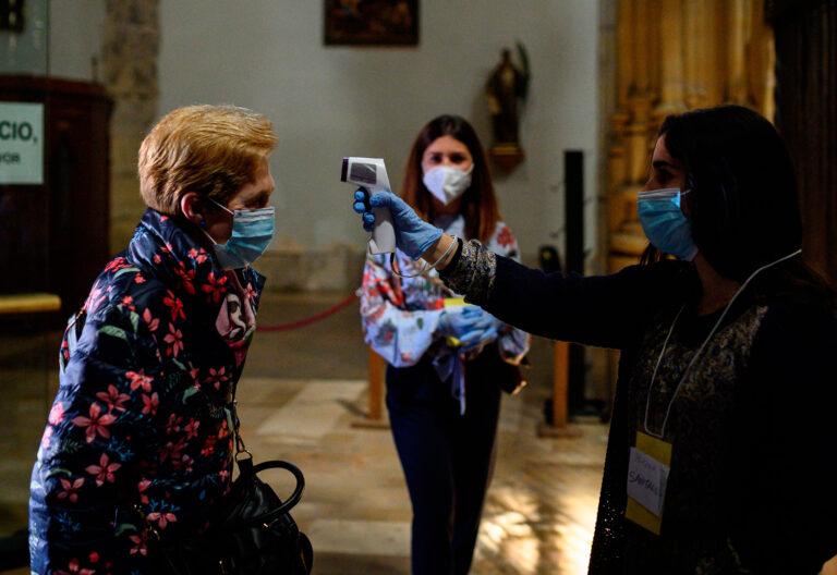 Una voluntaria toma la temperatura a los fieles que acuden a misa en la catedral de Alcalá de Henares