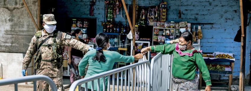 Una indígena pasa alimentos a una mujer en Cantagallo. Lima (Perú).