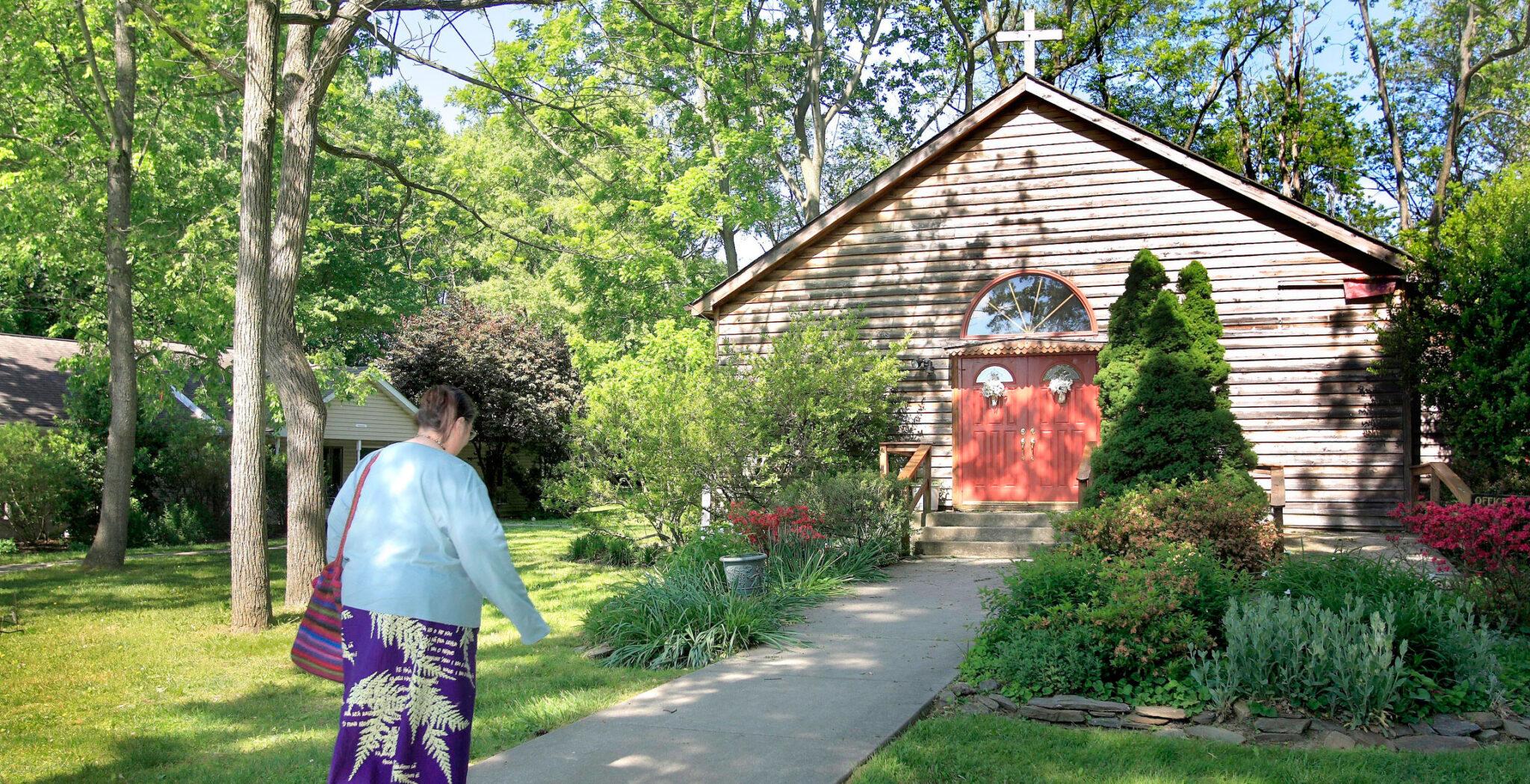 Mujer dirigiéndose a una capilla en el campo