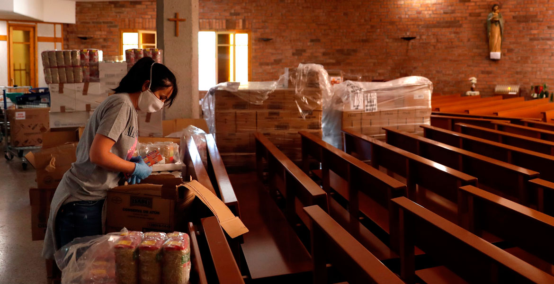 Una voluntaria organiza un lote de alimentos en la parroquia de Nuestra Señora de Bellvitge que la FundaciÛn La Vinya de L'Hospitalet de Llobregat