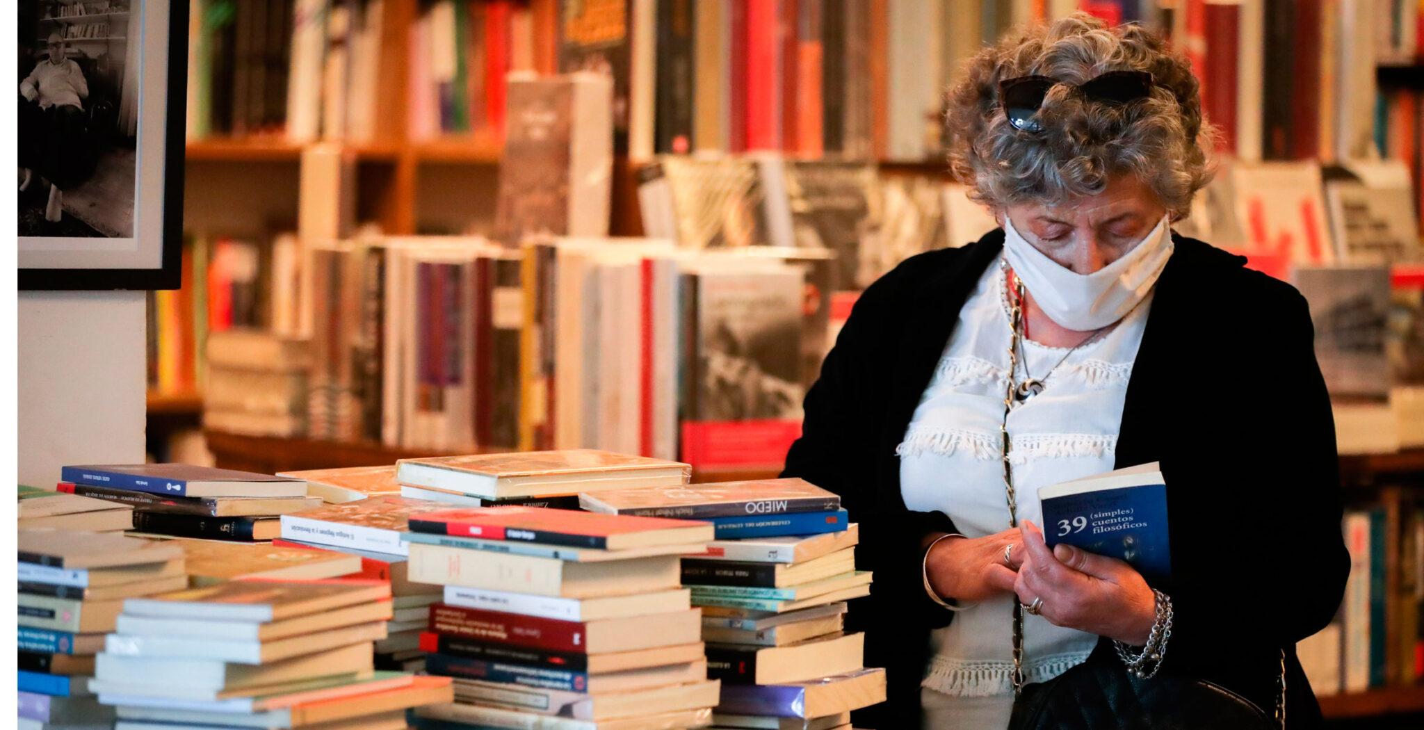 mujer revisando libros en una librería