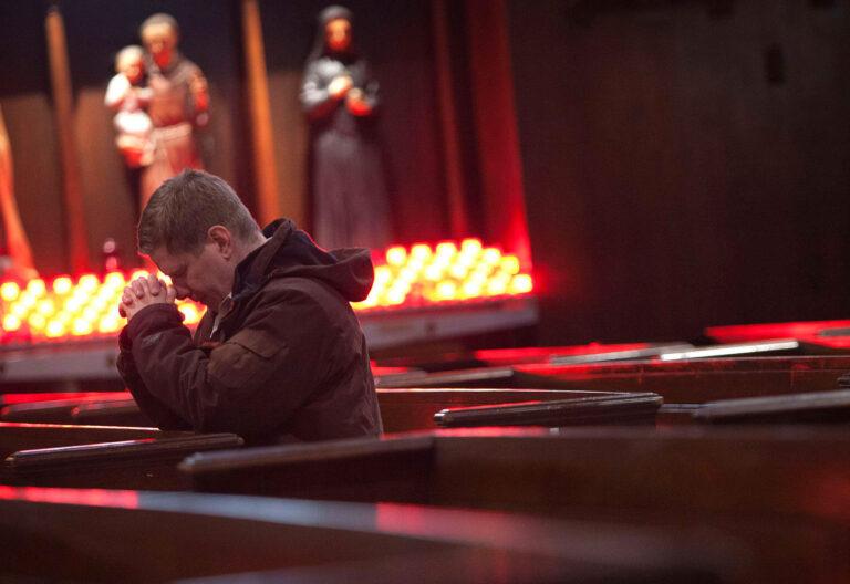 Un hombre reza de rodillas en una iglesia vacía (de fondo, varias imágenes de santos y un lampadario)