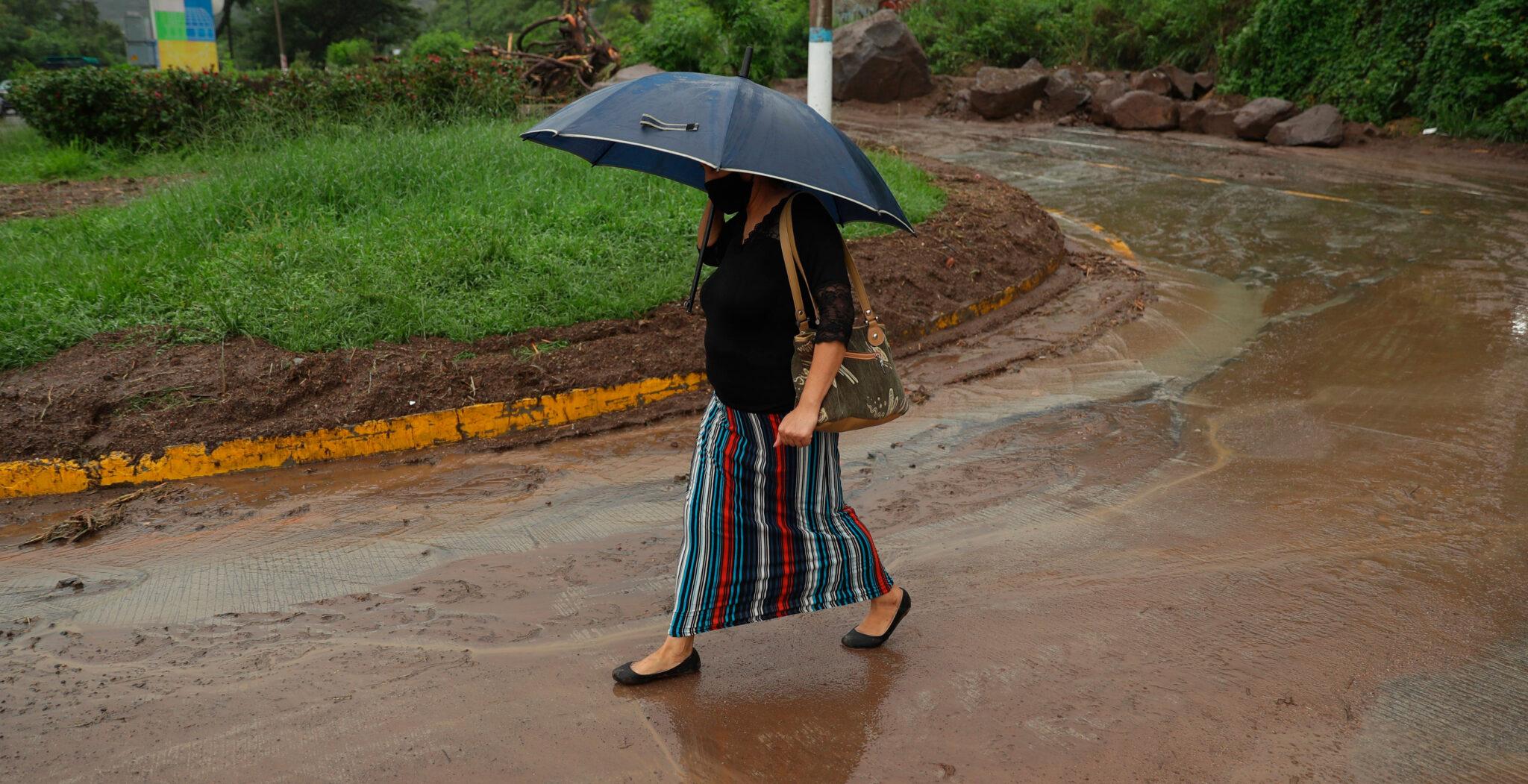 Mujer caminando bajo la lluvia en calle con barro