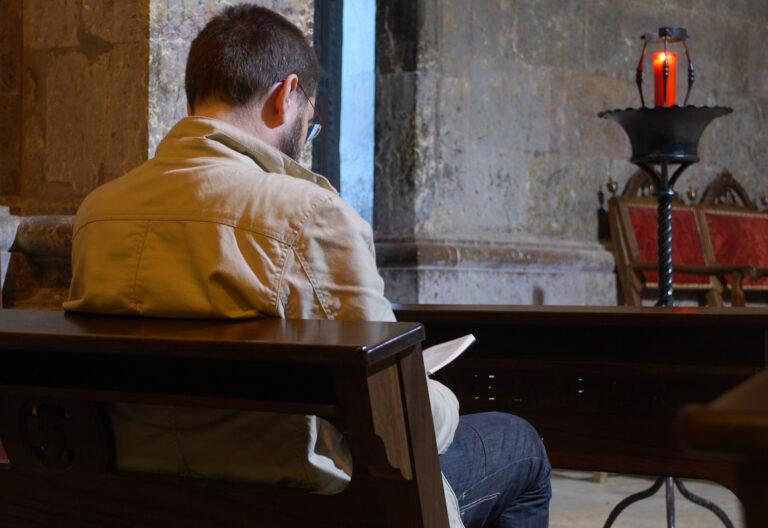 Hombre meditando en el banco de una iglesia
