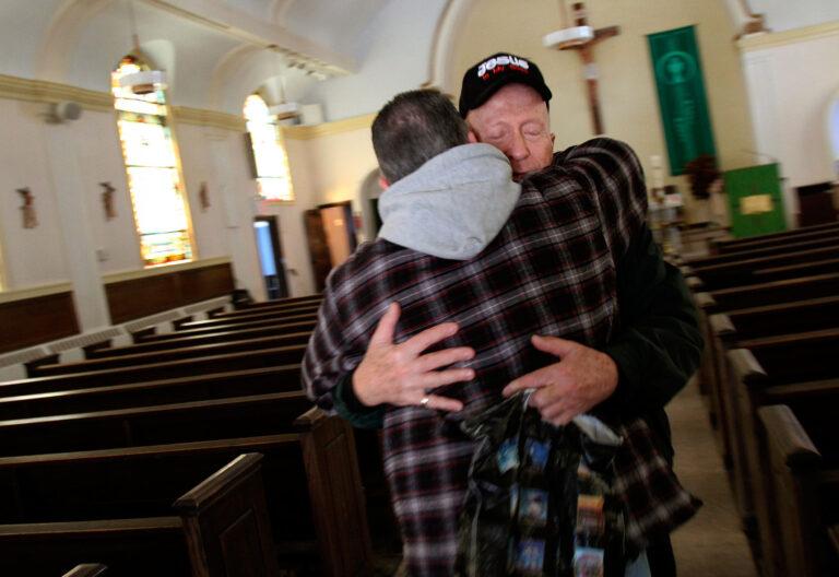 Un sacerdote acoge con una abrazo a un feligrés en medio de una iglesia vacía