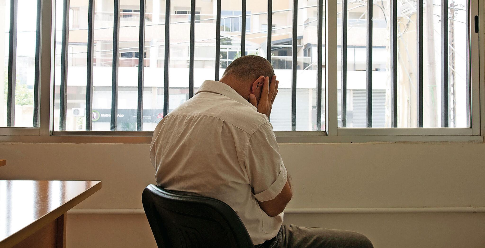 Hombre sentado de espaldas frente a una ventana con rejas y las manos en el rostro