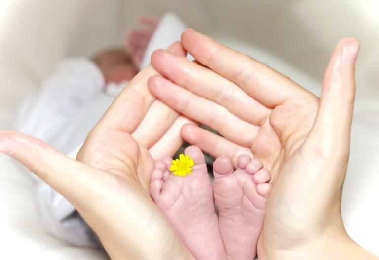 pies de bebé y manos de adulto